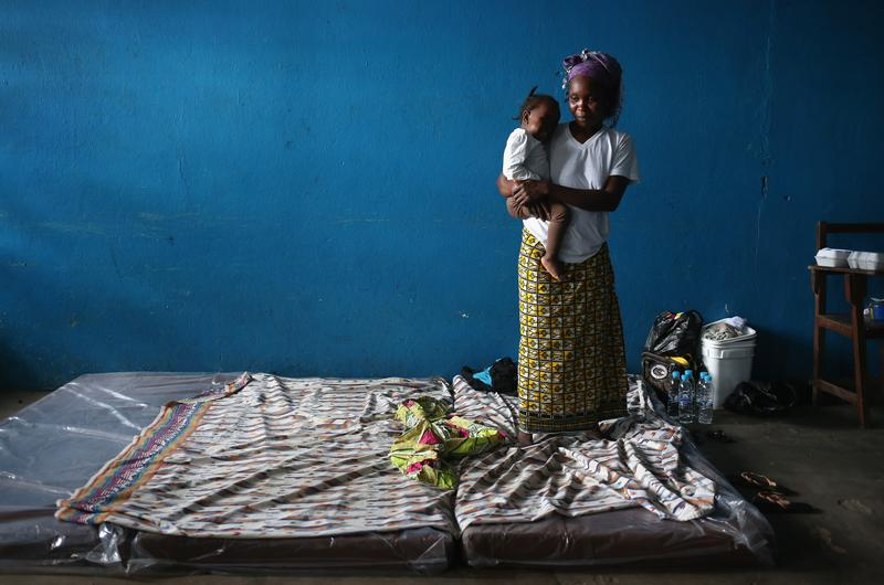 A mother and child stand atop their mattresses in a classroom now used as Ebola isolation ward on August 15, 2014 in Monrovia, Liberia.