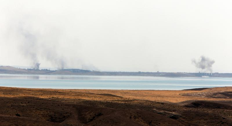 Smoke rises in the horizon following US airstrikes targeting Islamic State (IS) militants at Mosul Dam on the outskirts of the northern city of Mosul where insurgents are fighting Kurdish forces on Au