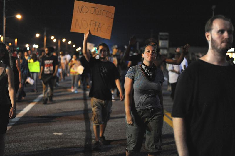 Demonstrators display signs during a protest on West Florissant Avenue in Ferguson, Missouri on August 18, 2014.
