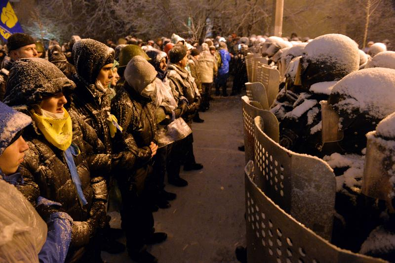 Pro-EU Ukrainian protesters stand opposite riot policemen securing the area outside the presidential office in Kiev on December 9, 2013.