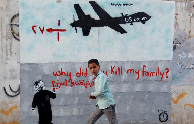 A Yemeni boy walks past a mural depicting a US drone and reading ' Why did you kill my family' on December 13, 2013 in the capital Sanaa.