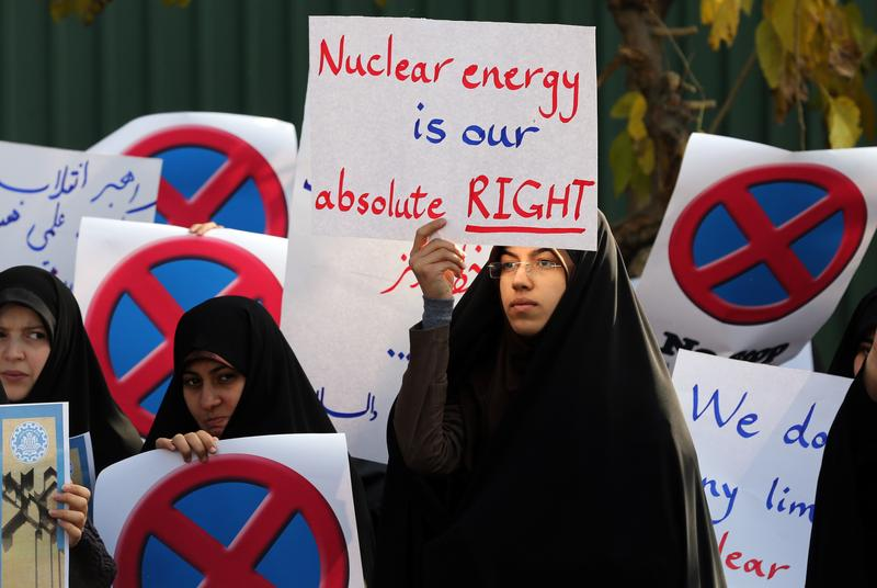 An Iranian student holds a placard reading 'Nuclear energy is our absolute right' during a demonstration outside the Tehran Research Reactor in the capital Tehran on November 23, 2014