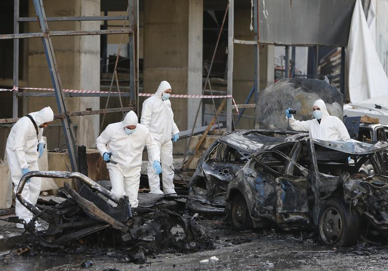 Lebanese forensic experts inspect the scene of a huge car bomb explosion that rocked central Beirut on December 27, 2013, killing Mohamed Chatah (Shatah), former finance minister and others.