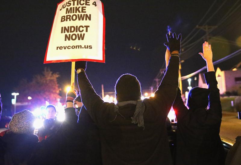 Demonstrators are confronted by police as they block a street during a protest ahead of the grand jury announcement on November 24, 2014 in Ferguson, Missouri.