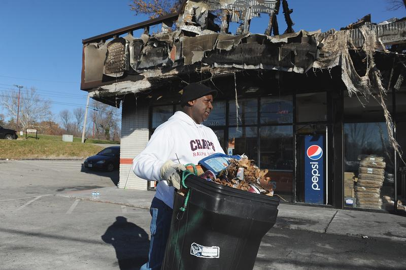 A volunteer helps cleanup at a burned out Little Caesars pizza restaurant in Ferguson, Missouri on November 25, 2014. Protesters set buildings ablaze and looted stores.