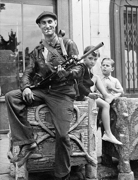 Watched by two small boys, a member of the French resistance (French Forces of the Interior) poses with his Bren gun at Chateaudun in 1944.