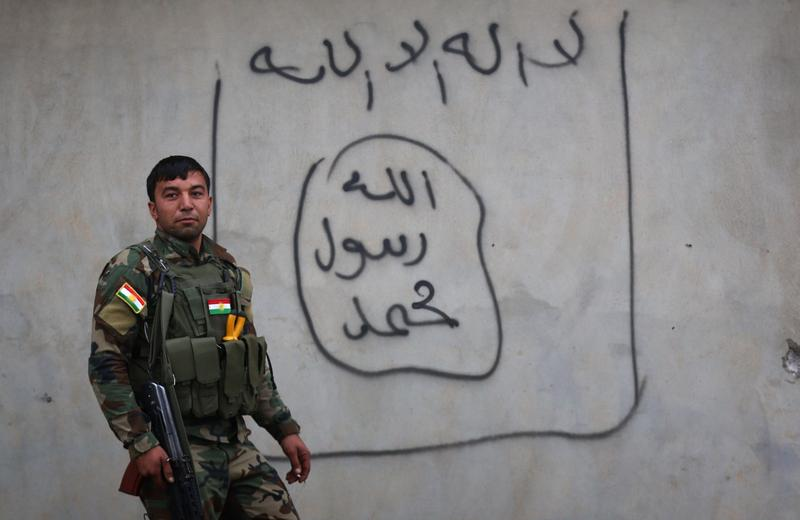 A Peshmerga fighter stands beside graffiti of the Islamic State (IS) group flag in Zummar city on December 18, 2014. Kurdish forces continue to battle IS fighters near Syria.