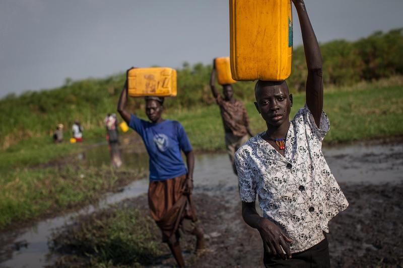 Women and children carry water in Minkammen on 01/08/14. Unrest began on 12/15/13 as a clash between army units loyal to South Sudan's President Salva Kiir and those loyal to ex-VP Riek Machar.