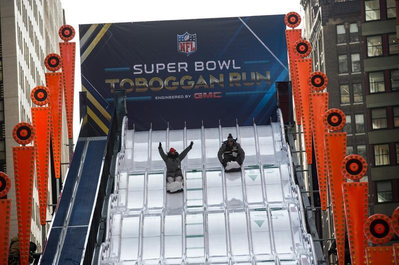 Sliding down the 'Super Bowl Toboggan Run,' set up as a part of Super Bowl Boulevard