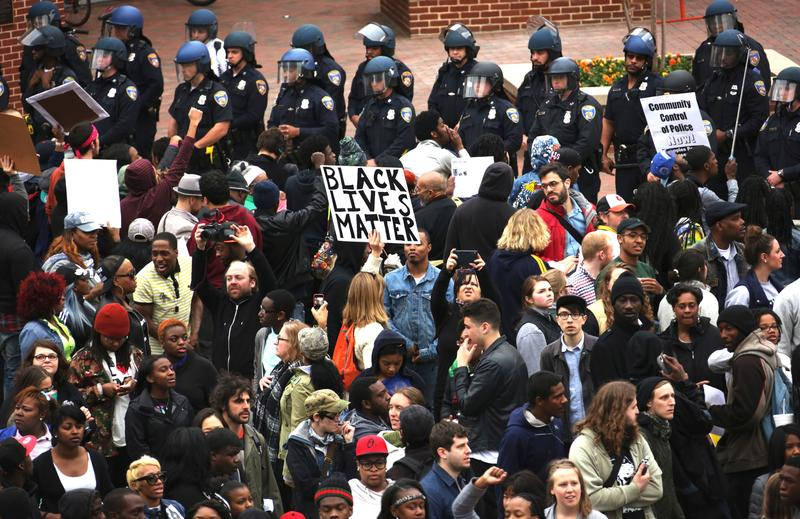 Protesters hold signs as they stand off with the police at Camden Yard during a march in honor of Freddie Gray on April 25, 2015 in Baltimore, Maryland.