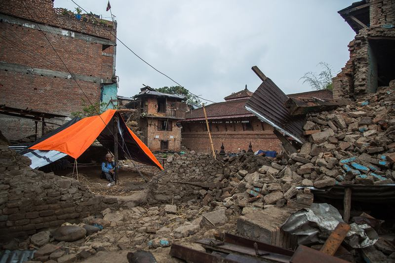 A man sits underneath a tent set up in front of his collapsed home on April 30, 2015 in Bungamati, Nepal.