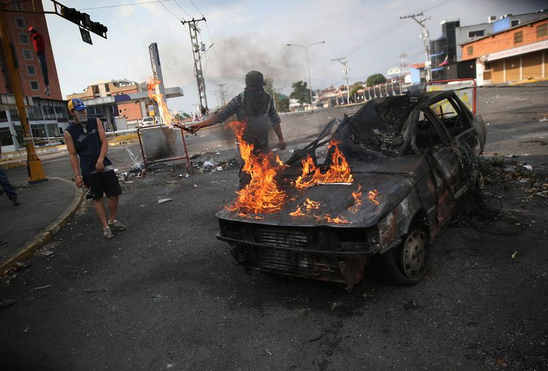 A protester throws gasoline on a burned out car during an anti-govenment protest on March 7, 2014 in San Cristobal, Venezuela.