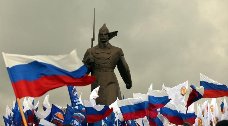 Pro-Kremlin activist hold Russian flags near a monument to Red Army soldier as they rally in the southern Russian city of Stavropol, on March 18, 2014, to celebrate the incorporation of Crimea.