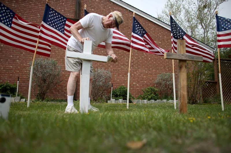 Bob Gordon paints a cross placed in front of 16 American flags as he helps build a memorial in front a church for the victims of the Fort Hood shooting on April 2, 2014.
