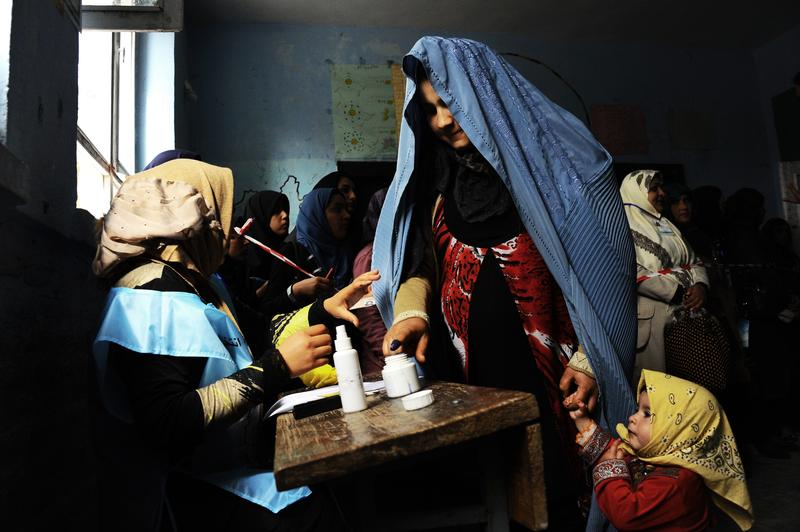 An Afghan woman (R) is guided by an official as she puts her finger in ink at a polling station in the northwestern city of Herat on April 5, 2014.