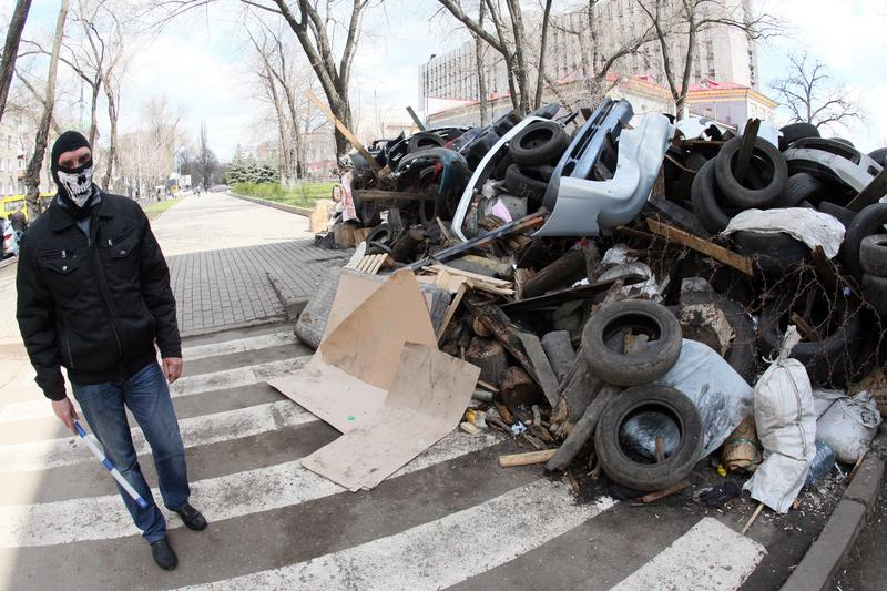 A pro-Russia activist guards a barricade outside the regional state building in the eastern Ukrainian city of Donetsk on April 15, 2014.