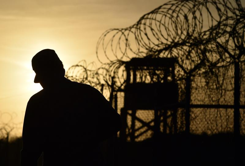 A U.S. soldier walking next to the razor wire-topped fence at the abandoned 'Camp X-Ray' detention facility at the US Naval Station in Guantanamo Bay, Cuba, April 9, 2014.