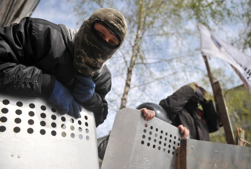 Pro-Russia activists guard a barricade outside the police regional building seized by the separatists in the eastern Ukrainian city of Slavyansk on April 17, 2014.