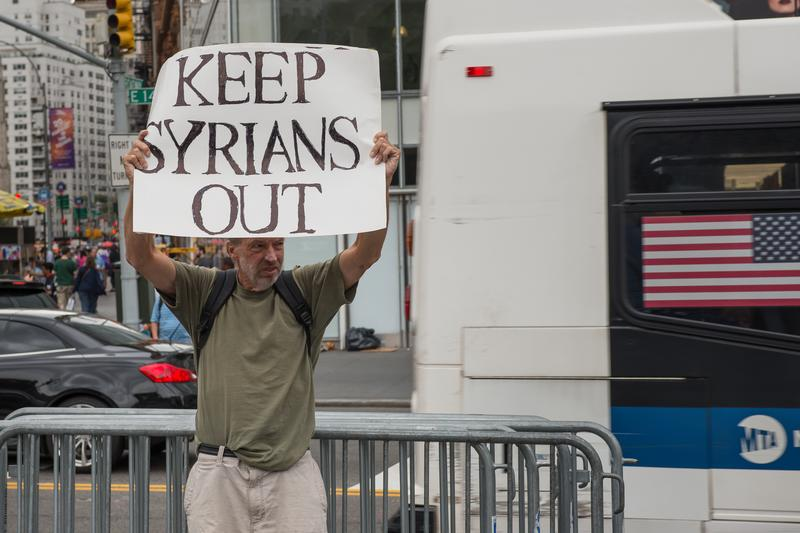 A lone counter -protester, James MacDonald stands on the curb declaring the opposite of the rally's message - Mr. MacDonald objects the proposed U.S. asylum for 10,000 refugees. September 12, 2015