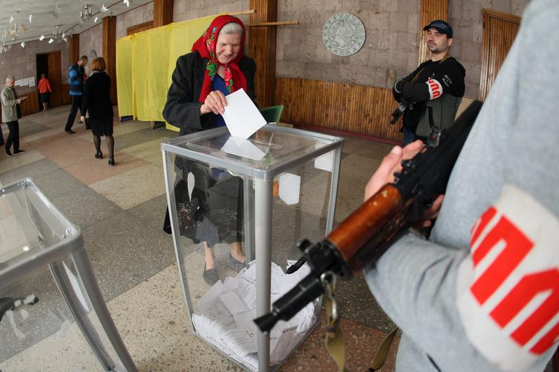 An armed pro-Russian activists stands guard as a woman casts her ballot for the referendum called by pro-Russian rebels to split from the rest of Ukraine, , on May 11, 2014 in Donetsk.