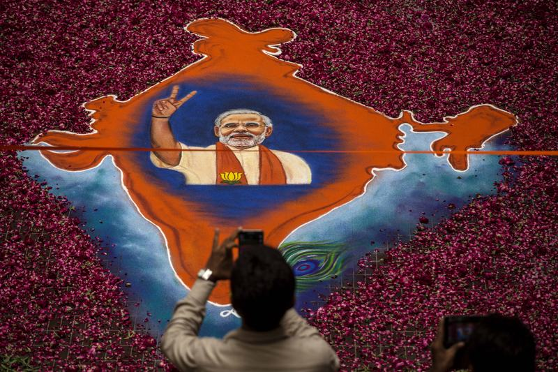 A supporter takes a picture of a map of India made of flowers with a picture of BJP leader Narendra Modi on it at the party's headquarters on May 16, 2014 in Ahmedabad, India.