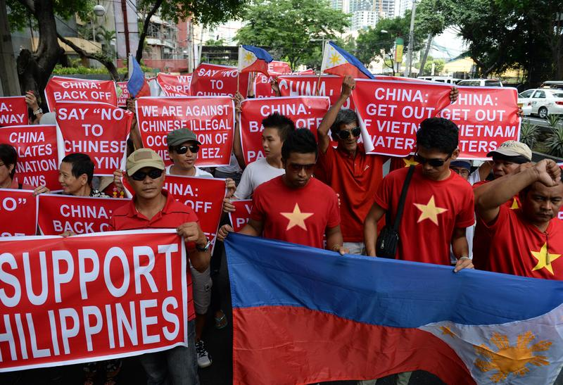 Philippine and Vietnamese protesters hold placards as they shout slogans during an anti-China protest in front of the Chinese consulate in the financial district of Manila on May 16, 2014.