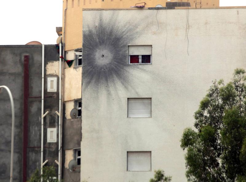 The impact of a rocket propelled grenade (RPG) marks the wall of a building on the road leading to the airport in Tripoli on May 19, 2014 following attacks by armed groups the previous day.