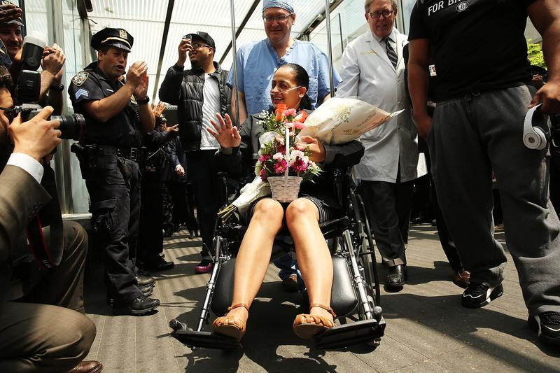 NYPD Officer Rosa Rodriguez is cheered by dozens of fellow officers as she is wheeled out of Weill Cornell Medical Center on May 19, 2014.