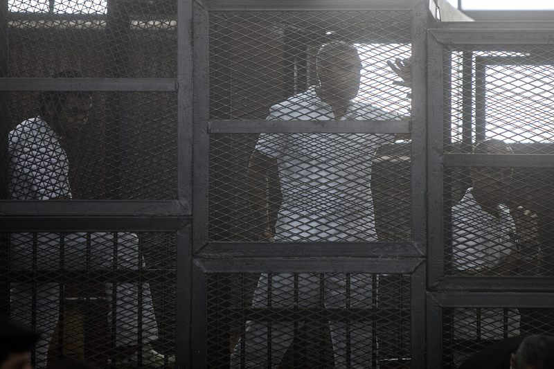 Australian journalist Peter Greste of Al-Jazeera his colleagues stand inside the defendants cage during March, 2014 trail proceedings at Cairo's Tora prison.