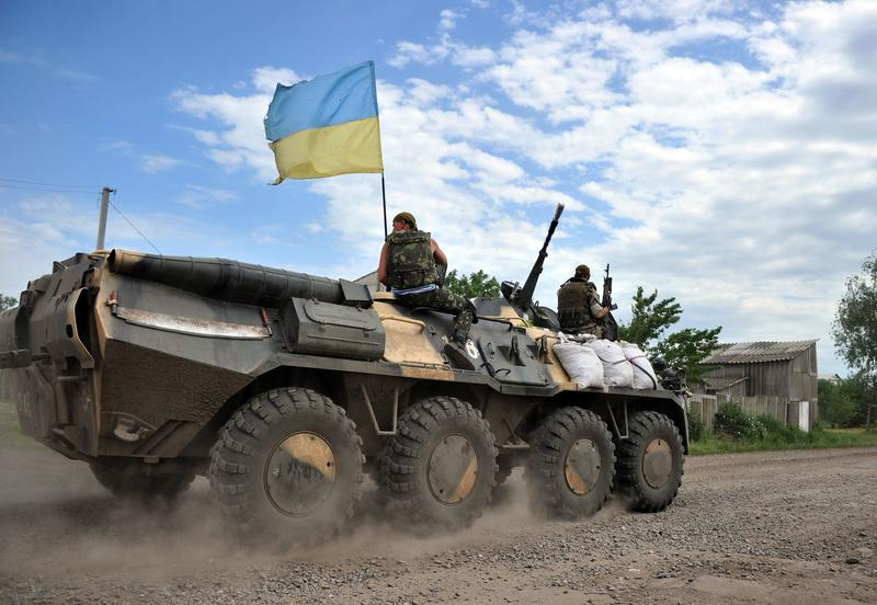 Ukrainian troops drive in Armoured Personnel Carriers through a small village bordering the Kharkiv and Donetsk regions, some 40 kilometers south of Izyum, on May 25, 2014.
