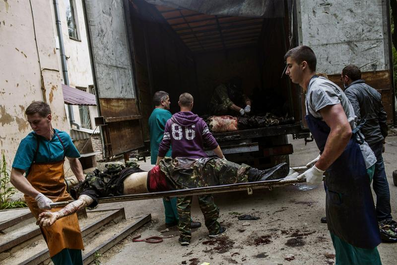 Medical workers and pro-Russian activists unload the bodies of killed pro-Russian fighters from a truck, in the eastern Ukrainian city of Donetsk, on May 27, 2014.