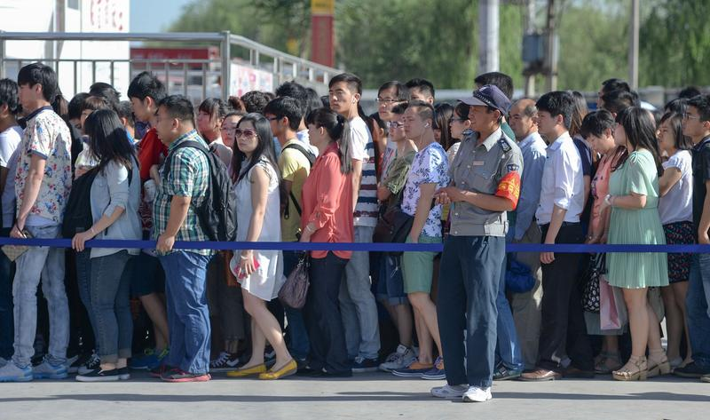 Beijing subway riders lining up outside a station to go through a security check before entering