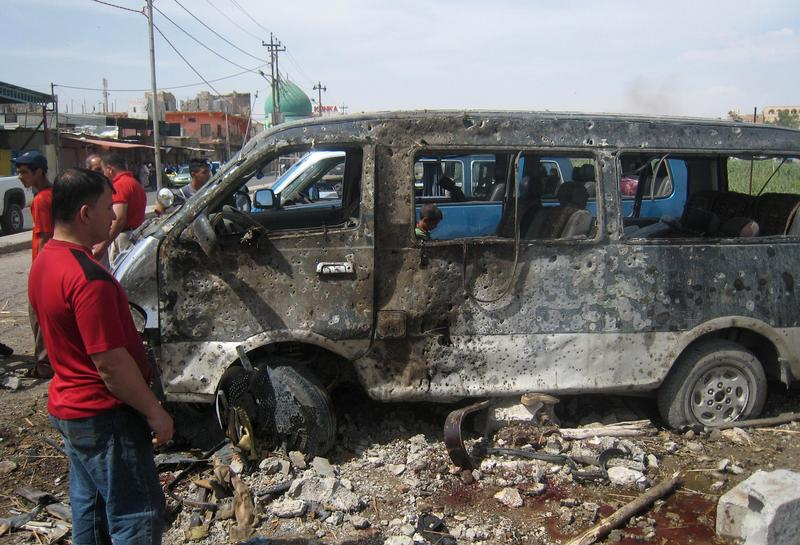 An Iraqi man looks at a destroyed mini bus at the site of car bomb attack in the northern city of Kirkuk on June 4, 2014.