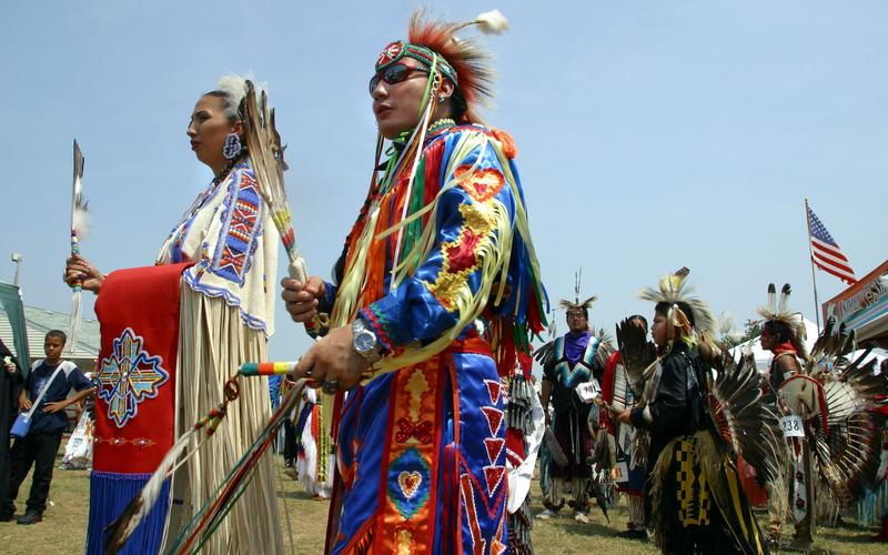 Head Man Delwin Fiddler (C) of the Lakota Sioux tribe and Head Lady Toni Tsatooke (L) of the Kiowa tribe lead dancers into a circle for the start of a Native American powwow in Urbana, MD. 08.04.2002