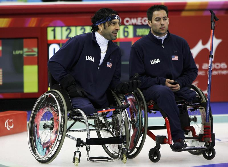 James Joseph (L) of the USA chats to team mate Augusto Perez during Wheelchair Curling match between the USA and Denmark on day three of the Turin 2006 Winter Paralympic Games on March 13, 2006.