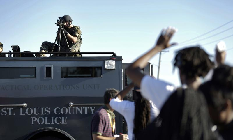 In this Wednesday, Aug. 13, 2014 file photo, a member of the St. Louis County Police Department points his weapon in the direction of a group of protesters in Ferguson, Mo.