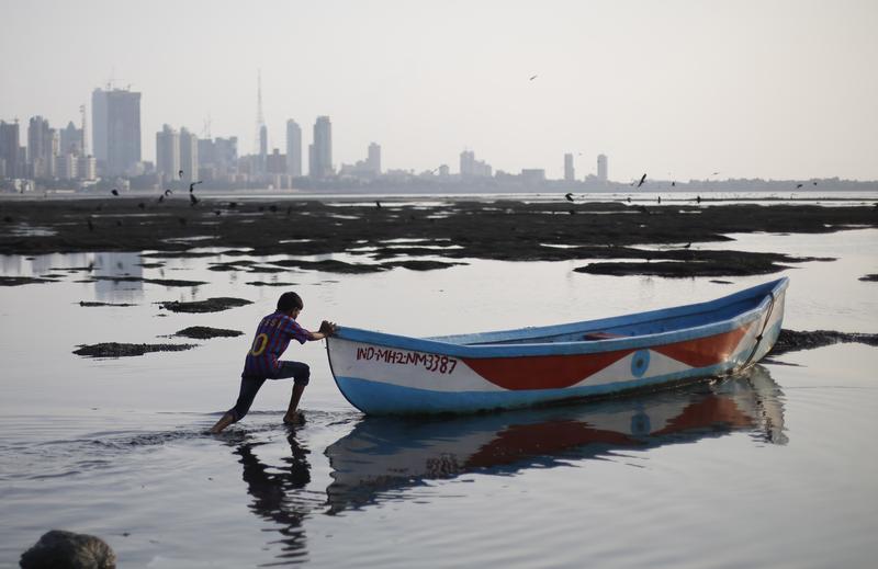 A boy pushes a boat as he plays near the shore of the Arabian Sea, in Mumbai, India, Sunday, Oct. 6, 2013.