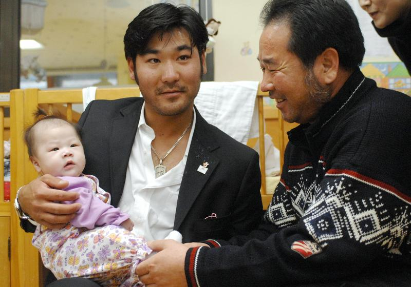 US Olympic skier Toby Dawson holds a baby in his arms as his South Korean father Kim Jae-Soo looks on while visiting a local adoption agency, Holt International Children's Service, in Seoul.