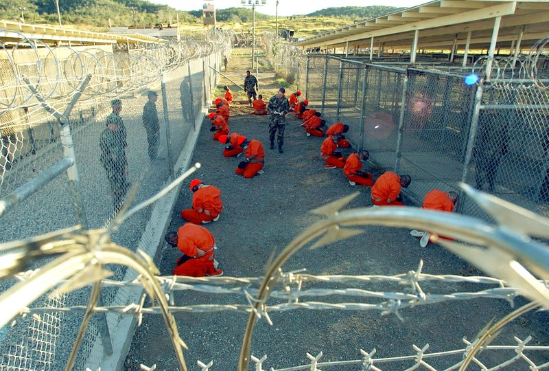U.S. Military Police guard Taliban and al Qaeda detainees in orange jumpsuits January 11, 2002 in a holding area at Camp X-Ray at Naval Base Guantanamo Bay, Cuba.