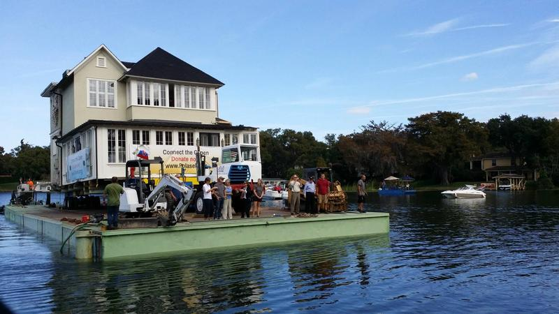 Onlookers watched as the first half of the Capen House, built in 1885, made its way across Lake Osceola to its new home