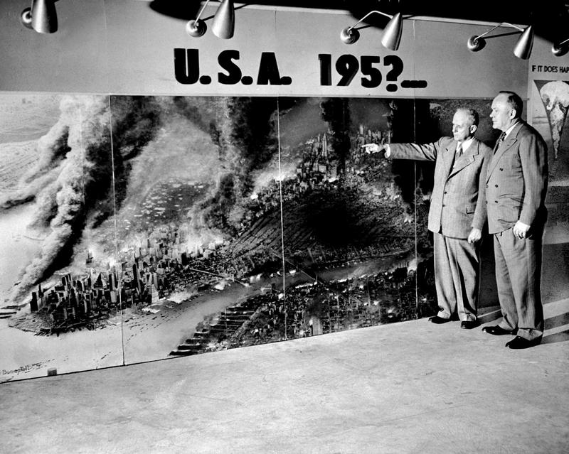 Lt. Gen. C.R. Huebner of the State Civil Defense Commission and Arthur Wallander (r), civil defense chief of NYC, with photo of projected results of an atomic bomb attack on NYC, Nov 28, 1951.