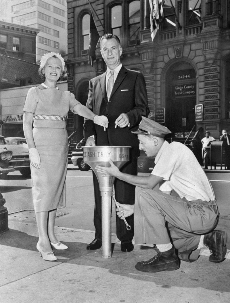 Margaret Lickdyke of the Citizens' Committee to Keep New York Clean, and Sanitation Commissioner Paul Screvane use new public ashtray installed by sanitation worker Frank Zwolinski. August 26, 1959.