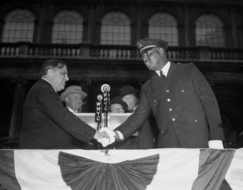 Sept 4, 1941: Mayor LaGuardia appointing Lt. Samuel J. Battle as member of Parole Commission. Police Commissioner Louis Valentine is center.