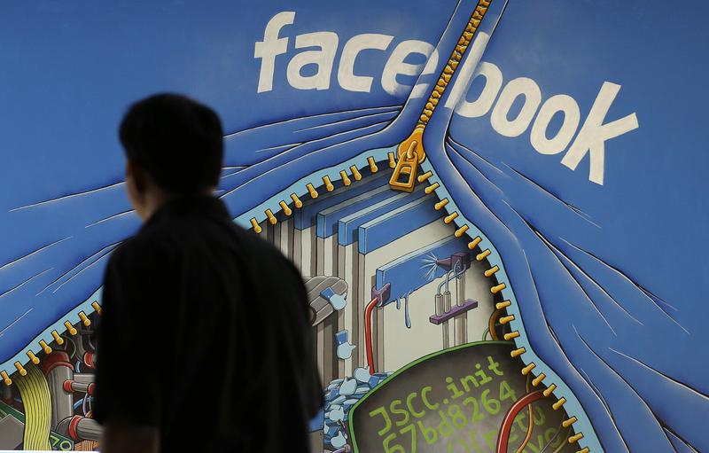 In this June 11, 2014 file photo, a man walks past a mural in an office on the Facebook campus in Menlo Park, Calif.