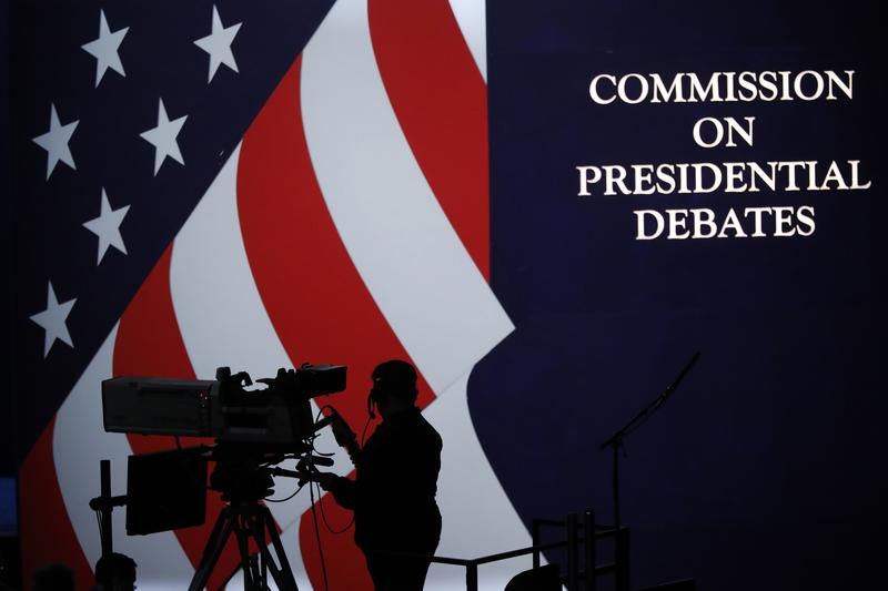 A cameraman is silhouetted against an American flag during preparations for the presidential debate at Hofstra University in Hempstead, NY, Sunday, Sept. 25, 2016