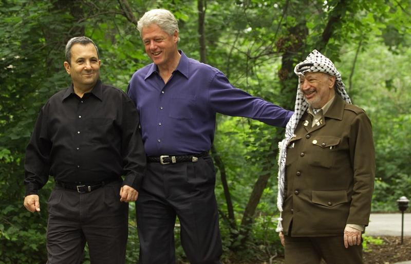 Then President Clinton, center, accompanied by Israeli Prime Minister Ehud Barak, left, and Palestinian leader Yasser Arafat, right, walk on the grounds of Camp David, Md.