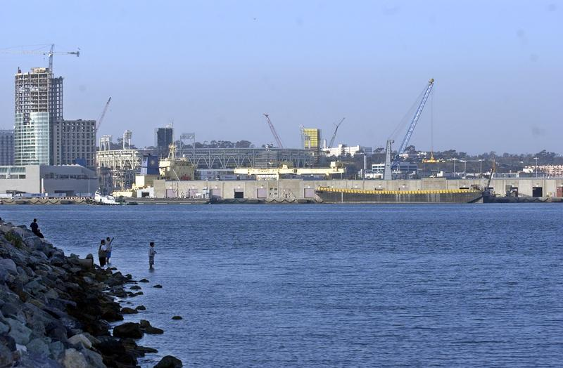 Fishermen wade into the water of San Diego Bay, Thursday, May 1, 2003, as a lone cargo ship sits at the Tenth Street dock of the San Diego port. Officials are debating a proposal to dredge the bay to