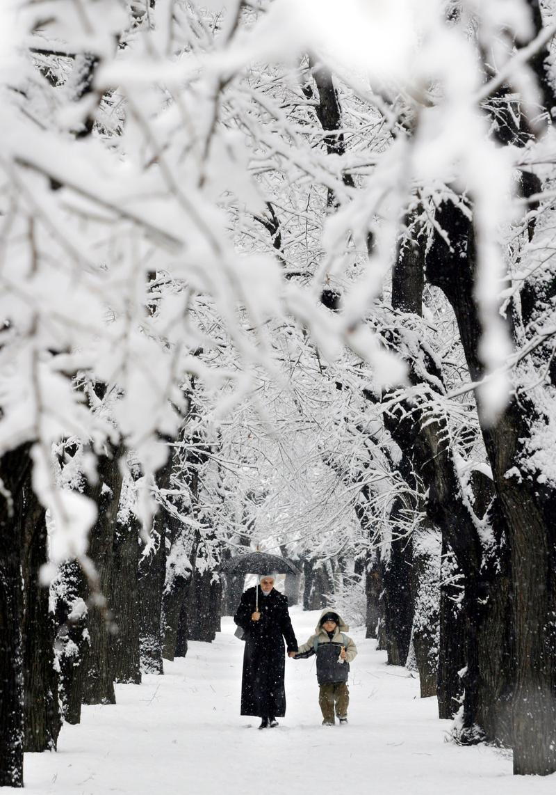 Mother and son walk on snow covered alley downtown Sarajevo, on Tuesday, Dec. 23, 2003. Snow cover deep up to 30 cm. and daily temperature up to minus 10 Celsius caused problems in traffic.