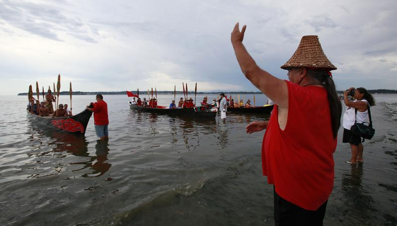 Nooksack tribal member George Adams signals to canoeists from Canada as they request permission to land in Birch Bay, Wash., July 25, 2009.