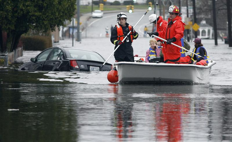 Firefighters in evacuate residents from a flood that hit West Warwaick, Rhode Island in March 2010.